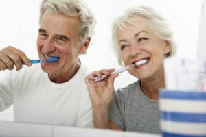 Senipr couple brushing their teeth