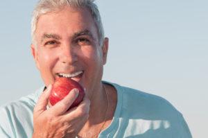 older man with dentures biting an apple