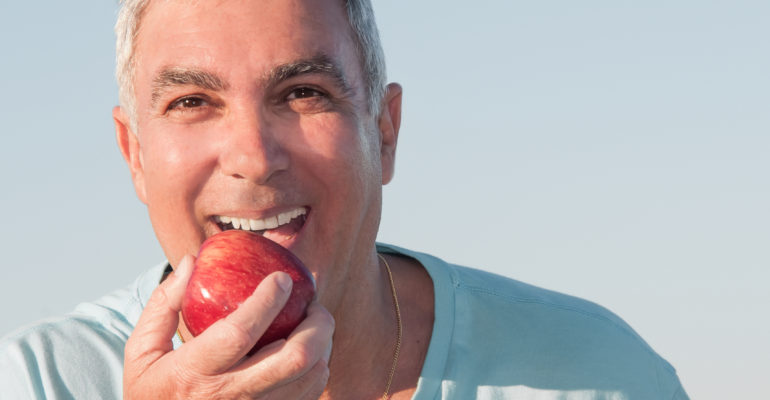 older man with dentures biting an apple