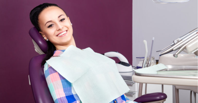 young women sitting in dental chair smiling