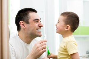 Dad and son brushing teeth together