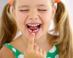 Little girl pointing to her missing tooth