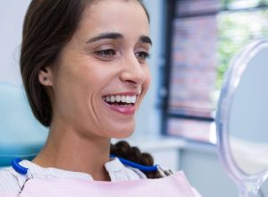 local dentist | patient smiling while looking at mirror.